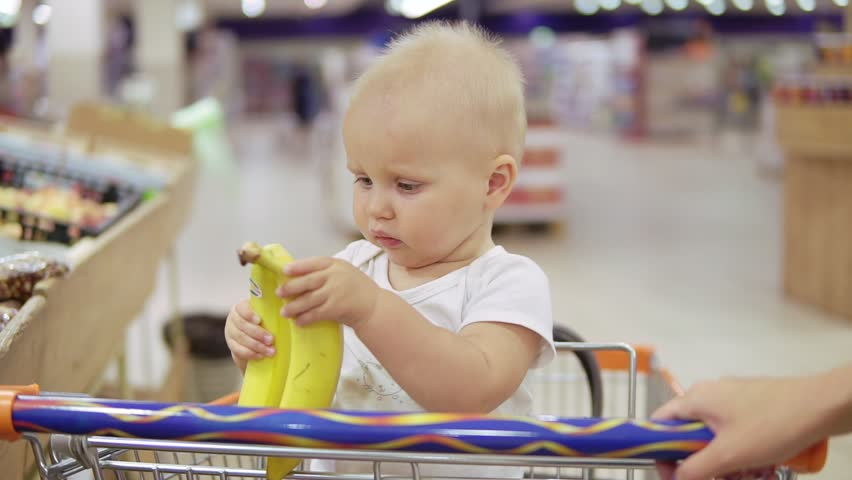Cute little child is helping her mother to choose bananas in the supermarket while sitting in a grocery cart and holding bananas, asking her mother to give her one