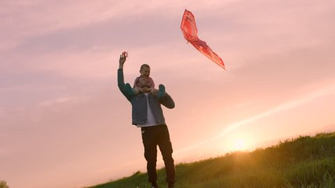 Happy family is playing flying kite at sunset. Son is sitting on his father's neck