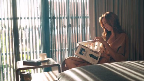 Girl sitting on chair in front of big window reading magazine