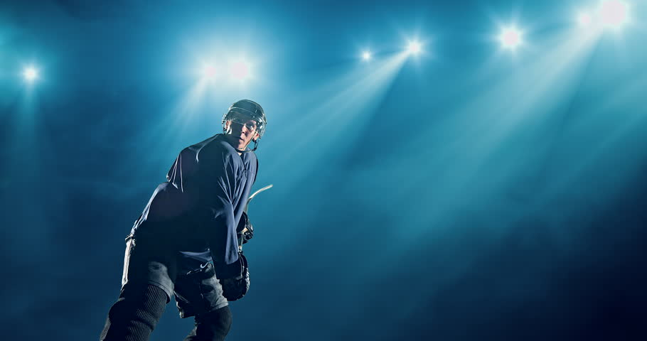 Ice Hockey player hits a puck on a dark background with intensional lens flares. He is wearing unbranded sports clothes.