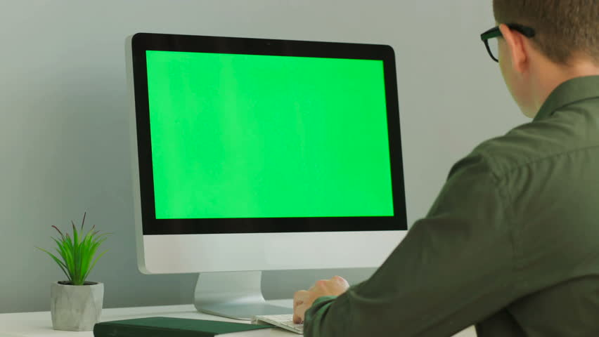 Close up shot of young man in the glasses using computer with green screen at the modern office table. Chroma key.