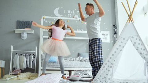 Joyful father and his little daughter dancing at home