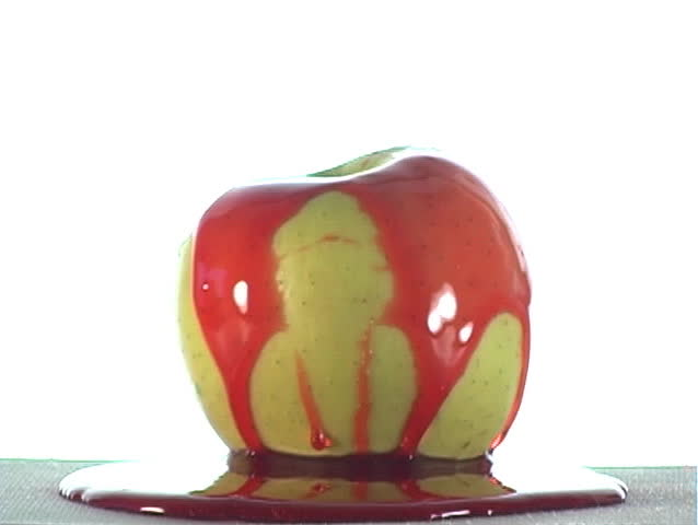 Special-effect:  red syrup lifts off of an apple.  The syrup could be cherry flavor, strawberry flavor, or ???
