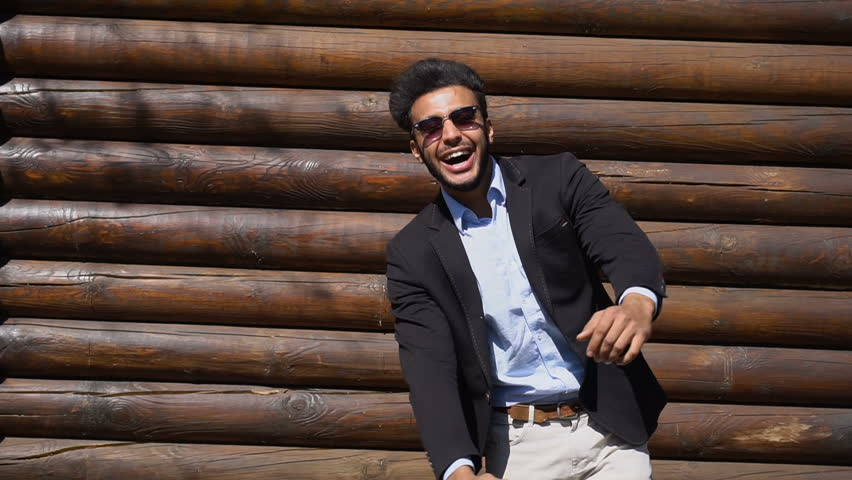 Slow motion, man from United Arab Emirates got excellent news and puts hands up and adjusts one s jacket in slow motion. Man has short dark hair, beard, dimples on cheeks and wears sunglasses. Concept