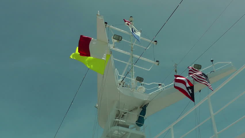 Colored flags on the upper part of a traveling cruise ship waving against a blue sky | Shutterstock HD Video #2992546
