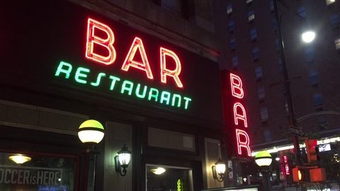 New York City Nighttime NX Establishing Shot CV of Bar Pub. Night exterior video footage of vintage neon sign. New York people go out at night to have fun, drink alcohol, go out on date, get together