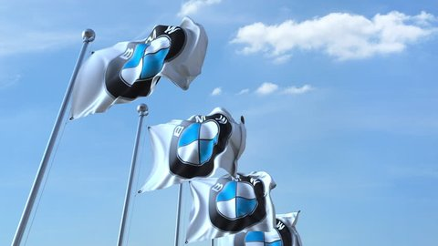 Waving flags with BMW logo against sky, seamless loop. 4K editorial animation