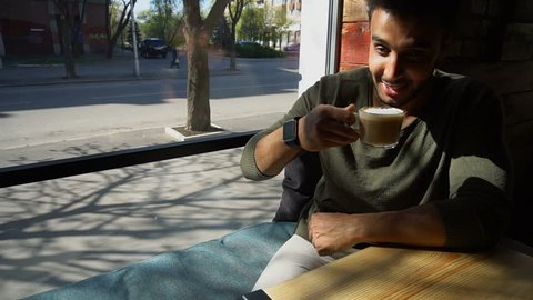 Handsome man sits near window and drinks coffee. Guy has short hair, beard and wears smart watch on hand. Boy dressed in khaki pullover. Concept of modern technologies for businessmen cafe for