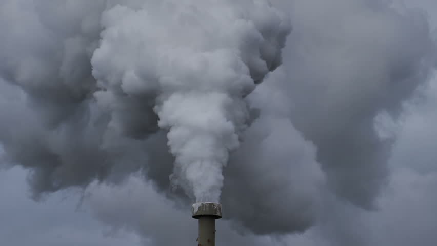 Billowing steam from smoke stack filling sky, super slow motion close up