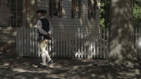 WILLIAMSBURG VIRGINIA - 2016. Re-enactment recreation of 1700s, Colonial Village, Town with houses, barns and taverns. Colonial Williamsburg streets and people.  Man in village in 18th century garb.