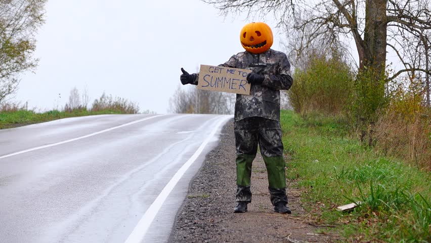 Poor pumpkinhead try to hitch ride back to summer, stay with written sign on road side, hold hand with thumb up. Rainy weather, empty country road. Man with carved pumpkin on head hitchhiking