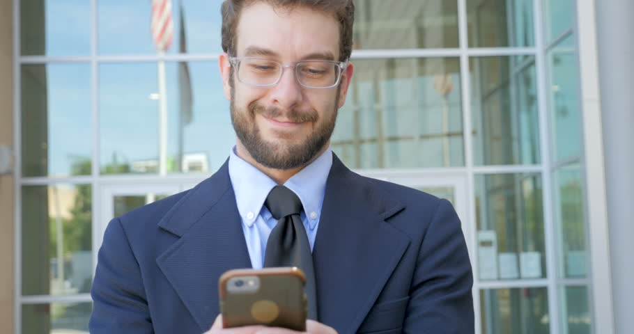 Happy attractive smiling millennial 30s businessman writing a text message email or social media post on smart phone outside a modern glass skyscraper with a reflection of an American flag