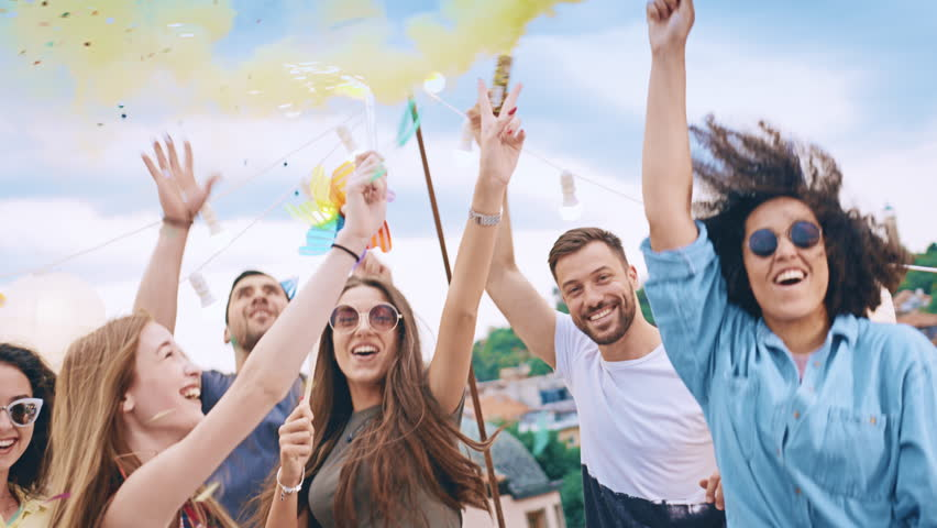 Diverse Young Party People On Rooftop Lifting Up Sparkler Fire In The Air In Colorful Smoke Holding Sparkler Fire In Rain Of Confetti Relaxation And Joy Friendship Concept At Sunset Shot on Red Epic W