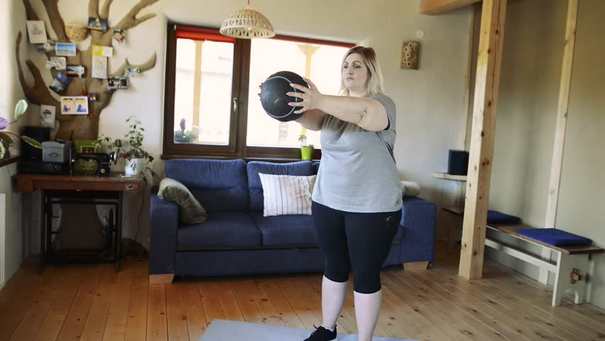 Attractive overweight woman at home working out with medicine ball. | Shutterstock HD Video #30019816