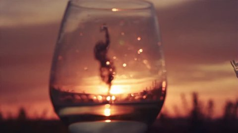 Silhouette of a dancing woman out of focus through a glass with white wine