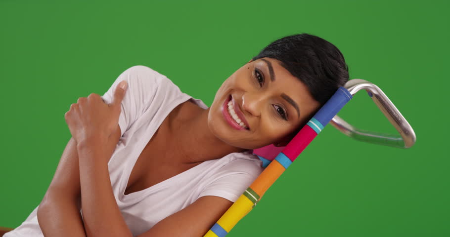 Portrait of black female lounging, looking at camera with joyful smile on green screen. On green screen to be keyed or composited.