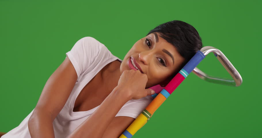 Portrait of young black female talking to camera and smiling on green screen. On green screen to be keyed or composited.