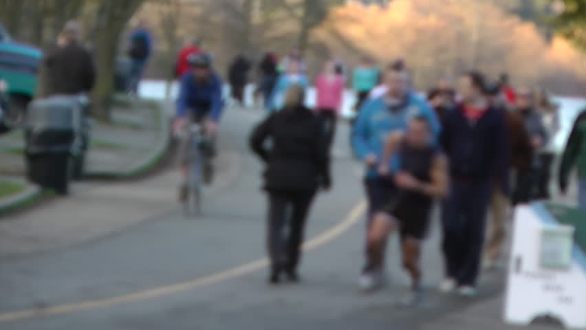 SEATTLE, WASHINGTON, JAN. 2012.  Known for healthy lifestyles, Seattle joggers, walkers & bikers exercise in cool, late sunny weather around Green Lake. Soft focus. There's even a dog among the crowd. #3004066