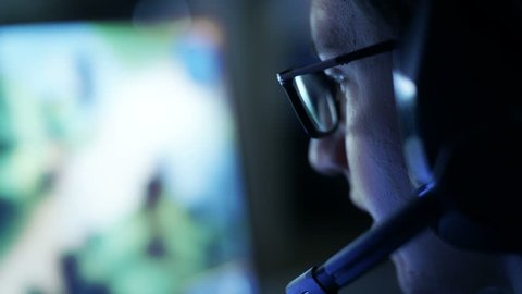 Professional Gamer Plays in MMORPG/ Strategy Video Game on His Computer. He's Participating in Online Cyber Games Tournament, Plays at Home, or in Internet Cafe. He Wears Glasses and Gaming Headsets.