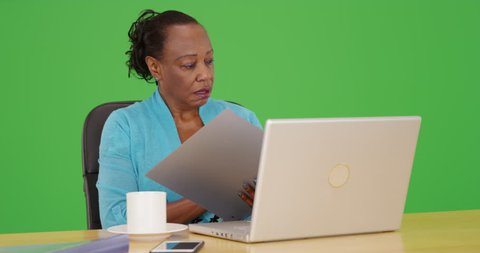 An African American businesswoman uses her laptop at her desk on green screen. On green screen to be keyed or composited.