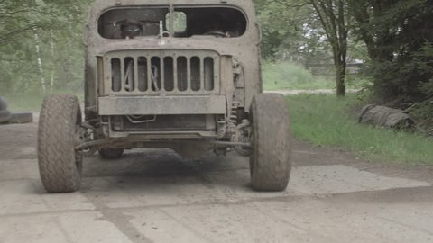 Post apocalyptic car in post apocalyptic landscape drive through the mud. Two persons inside. Slow motion, s-log, ungraded