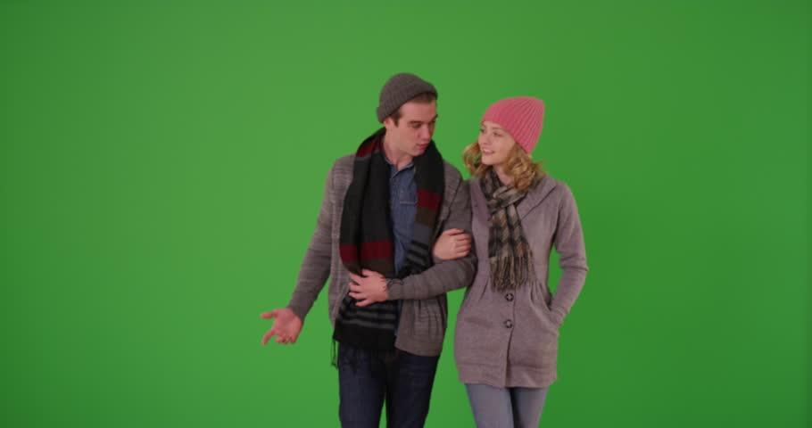 Young couple or friends in winter clothes taking a walk and using cell phone for directions on green screen. On green to be keyed or composited.