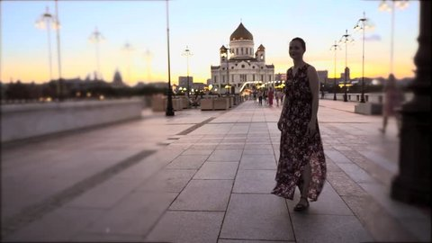 Young woman walking on the illuminated Patriarshy bridge towards the Cathedral of Christ the Saviour, Moscow, Russia. Camera follows behind. Selective focus shot