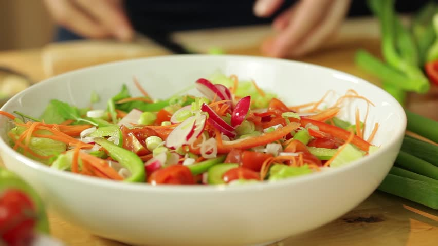 Dolly shot of female hands putting slices of vegetables into bowl in kitchen surrounding