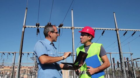 Engineer and Worker at Electrical Substation.