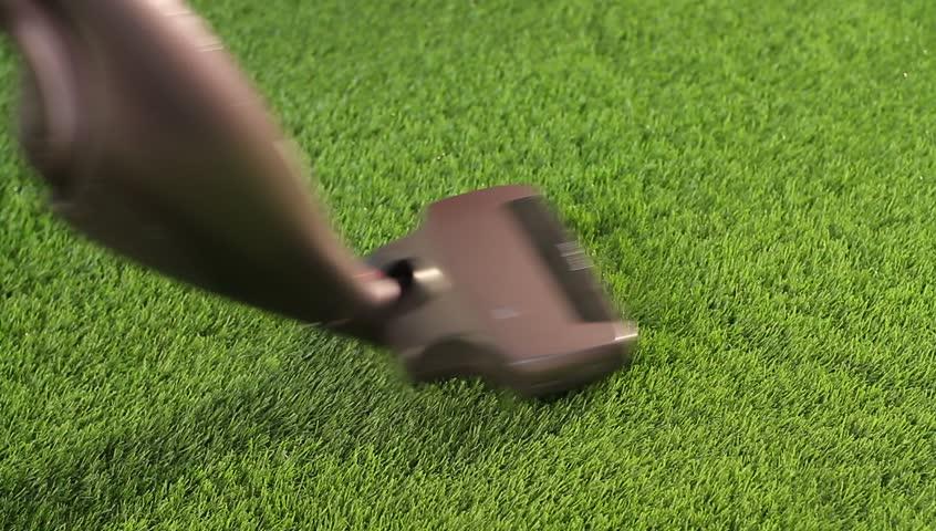 A household vacuum on grass carpet