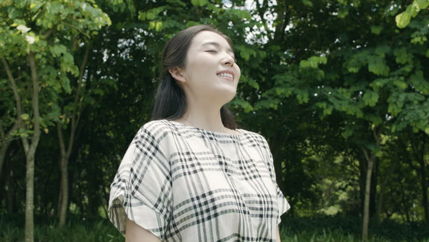 pretty asian woman taking deep breath, smiling & enjoying nature outdoor