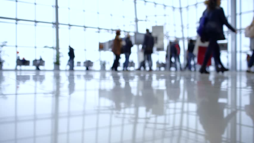 People out of focus walk inside a bright, modern building. Focus in the foreground | Shutterstock HD Video #30157090
