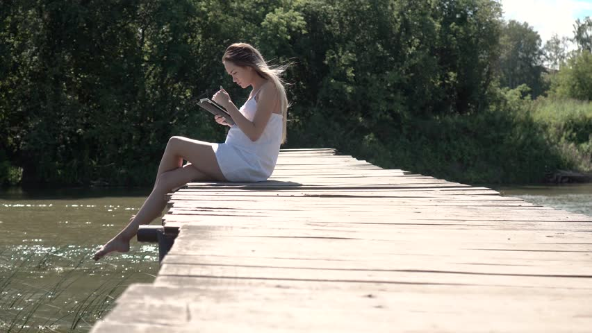 Attractive pregnant 20s female in white dress use a digital tablet while sitting on a wooden bridge across the river 4k. | Shutterstock HD Video #30177196