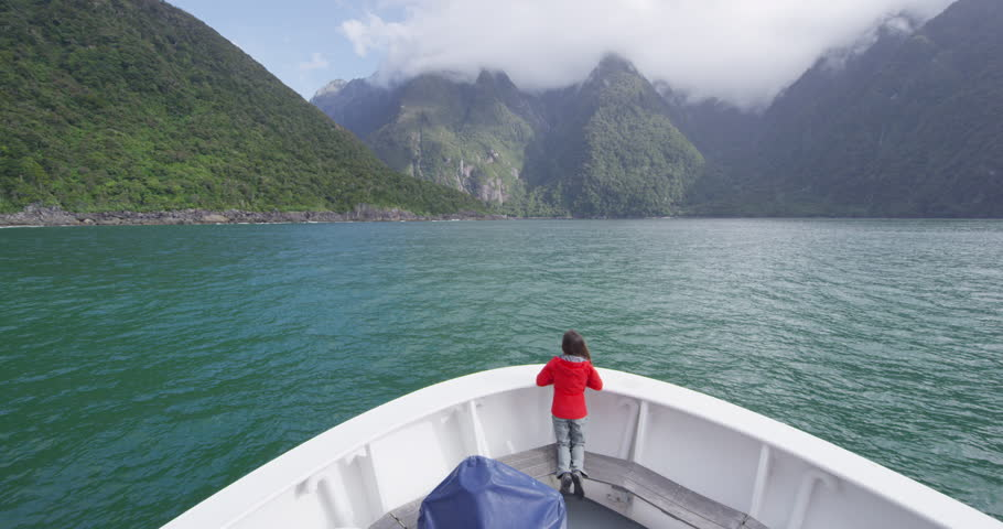 Cruise ship in New Zealand Milford Sound Fiordland National Park. Tourist enjoying boat tour and amazing view of fjord in most famous travel destination in New Zealand.