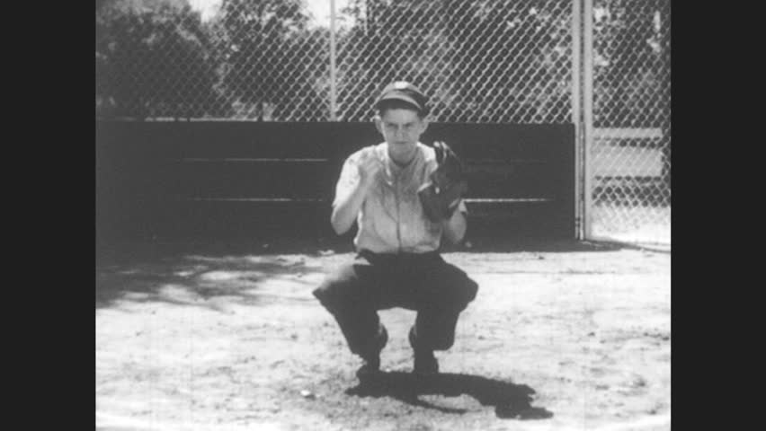 1950s: Boy playing catcher in baseball. Pitcher throws softball. Catcher catches softball and throws it back. Man in suit talks while holding notebook forward.