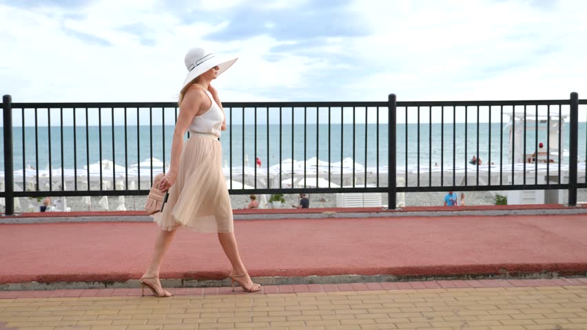 An elegant woman in a hat and a white air dress strolls along the waterfront. General shooting. 4k, slow-motion