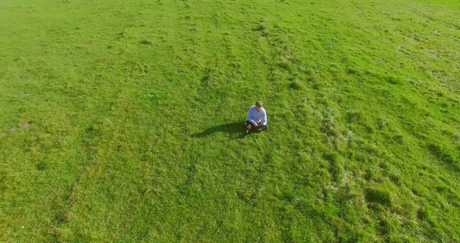 UHD 4k aerial view. Low orbital flight over businessman sitting on green grass with notebook (pad) at yellow rural wheat field. Radial movement. | Shutterstock HD Video #30196756