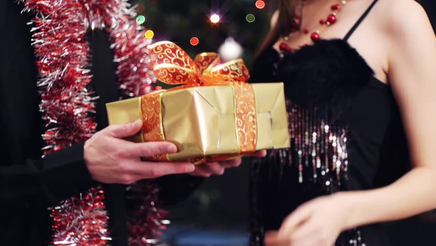 young man giving gift to his girlfriend at party