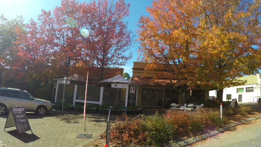 ADELAIDE, SOUTH AUSTRALIA - MAY 16, 2017: Automobile POV driving along beautiful Autumn tree lined streets of Stirling in the Adelaide Hills, passenger view.