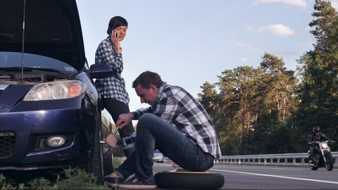 handsome caucasian man changing a tire on the side of the road. Young woman wearing casual clothes has phone conversation on smartphone . Female looking on the guy and smiling.