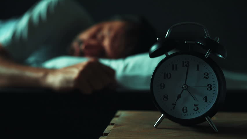 Restless man at night in bed trying to fall asleep stock footage restless man lying in his bed in morning selective focus on bedside table with vintage ccuart Gallery