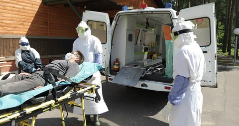 MINSK, BELARUS - JULY 31, 2017: Medical training by Ebola virus protection. Group of doctors or nurses wearing uniform ?arry patient on stretcher to the ambulance car. 4K footage.
