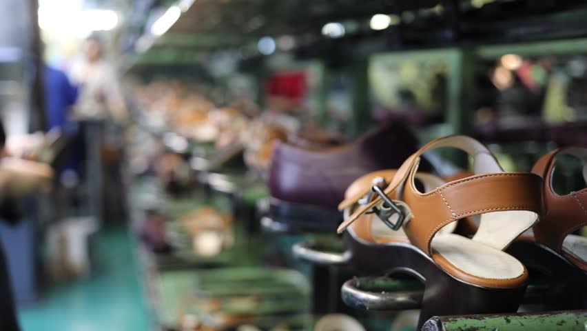 Shoes on conveyor in factory, working people out of focus, close-up, slow motion