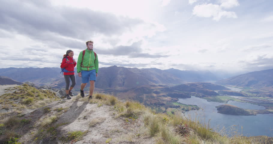 Hikers hiking up famous hike to Roys Peak on South Island, New Zealand. Couple tramping enjoying outdoor active lifestyle in beautiful nature on famous tourist destination, New Zealand. SLOW MOTION.
