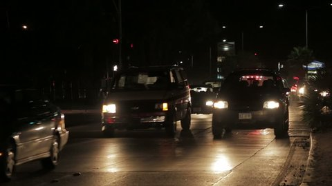Ambulance breaking through in traffic by night, answering an emergency call