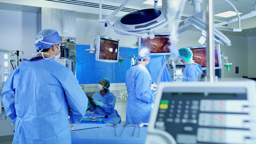 Multi ethnic medical hospital specialist team in scrubs training in the operating theatre in Laparoscopy surgery using Endoscope technology with monitor equipment RED WEAPON   Shutterstock HD Video #30270496