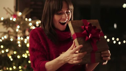 Amazed young woman looking at magical christmas gift in the box