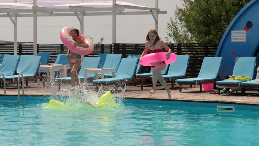 4de499059a girls in bathing suit resting by poolside with mattress and inflatable  ring, jump into blue water,