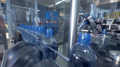 Power operated PET water bottle preparation assembly.