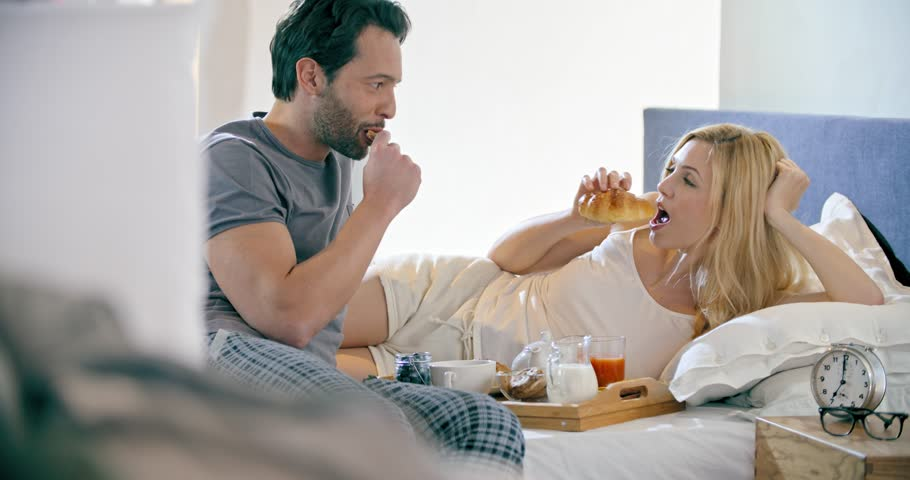 Beautiful man and woman eating breakfast with brioches in bed.Couple in love morning wake up at home in bedroom. Caucasian girlfriend and boyfriend people liying on bed. Lovely strokes. 4k video